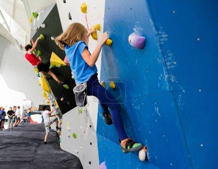 Photo pour Femme caucasienne active enfant est sur le mur d'escalade - image libre de droit