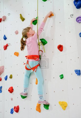 Photo for Active caucasian girl on the climbing wall - Royalty Free Image