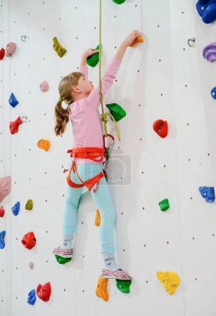Photo pour Actif caucasien fille sur l 'escalade mur - image libre de droit