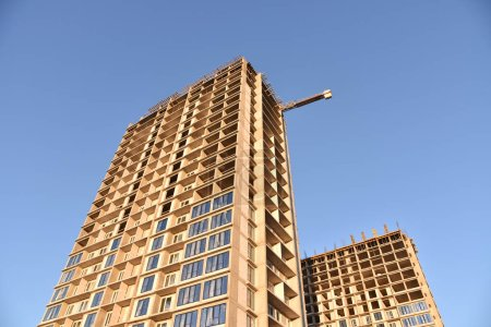 Photo pour Construire le bâtiment de grande hauteur. Installation de fenêtres à double vitrage avec cadres en uPVC dans un nouveau gratte-ciel résidentiel sur fond bleu ciel. Projet de rénovation de maisons hautes, programmes gouvernementaux - image libre de droit