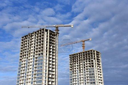 Photo pour Des grues à tour construisent le bâtiment de grande hauteur. Grue travaillant sur le chantier. Nouveau gratte-ciel résidentiel sur fond bleu ciel. Projet de rénovation de maisons hautes, programmes gouvernementaux - image libre de droit