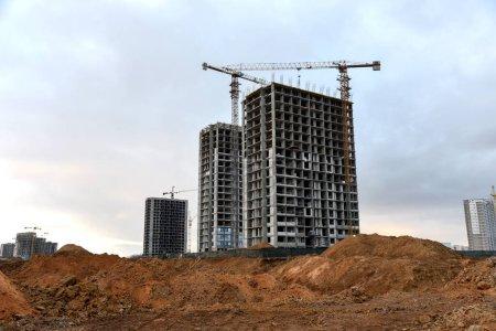 Photo pour Des grues à tour construisent les immeubles de grande hauteur. Grue travaillant sur le chantier. Nouveau gratte-ciel résidentiel sur fond de coucher de soleil. Projet de rénovation de maisons hautes, programmes gouvernementaux - image libre de droit