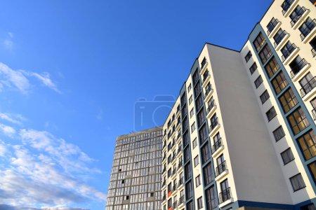 Photo pour Façade d'un nouveau bâtiment résidentiel moderne de grande hauteur. Gratte-ciel sur fond bleu ciel. Projet de rénovation de maisons hautes, programmes gouvernementaux. Maison multi-étages minimaliste. Architecture urbaine - image libre de droit