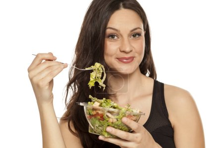 Photo for Young beautiful woman eating Caesar salad on a white background - Royalty Free Image