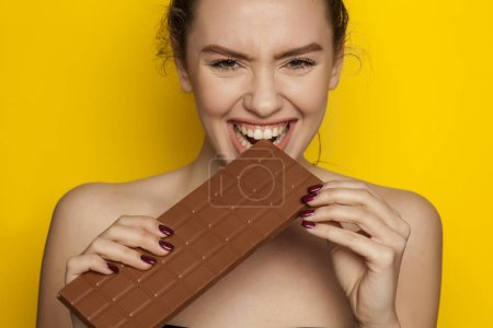 Feliz joven mujer disfrutando de comer chocolate sobre un fondo amarillo