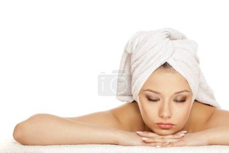 Photo pour Jeune fille avec une serviette sur la tête posant sur un fond blanc - image libre de droit