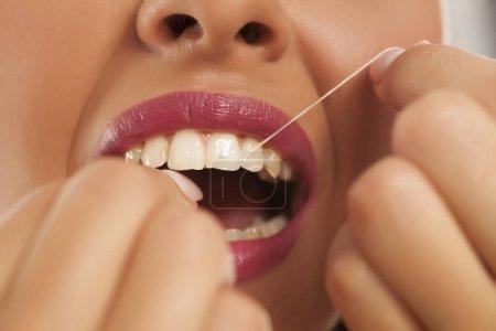 Photo pour Jeune belle femme nettoie ses dents avec de la soie dentaire - image libre de droit