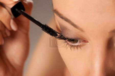 Photo for Young woman applying mascara on white background - Royalty Free Image