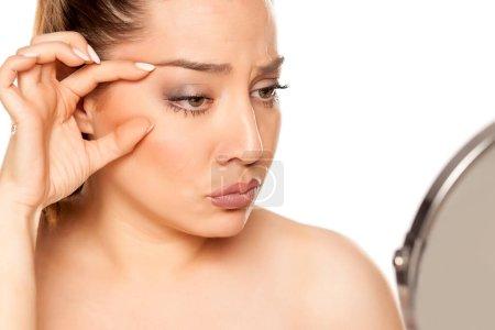 Photo pour Portrait de belle jeune femme serrant les rides autour de ses yeux sur fond blanc - image libre de droit