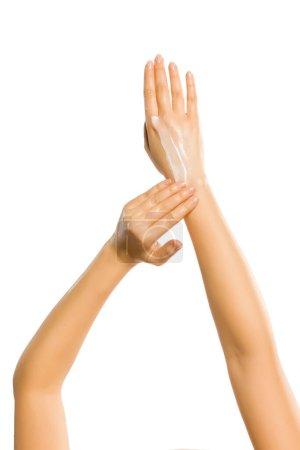 Photo pour Gros plan de mains féminines appliquant crème pour les mains sur fond blanc - image libre de droit