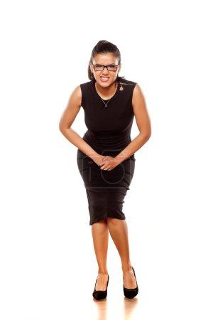 Photo pour Belle jeune femme dans une robe noire serrée a besoin d'uriner - image libre de droit
