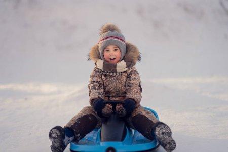 Foto de Niño emocionado sentado en el trineo y mirando a la cámara después de ir abajo de la colina - Imagen libre de derechos