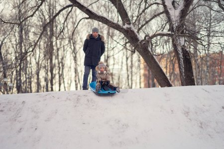 Photo for Father and son on sleigh starting to sled down the hill in the park - Royalty Free Image