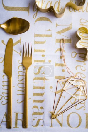 Photo for Top view of golden table setting on white surface with letterings - Royalty Free Image