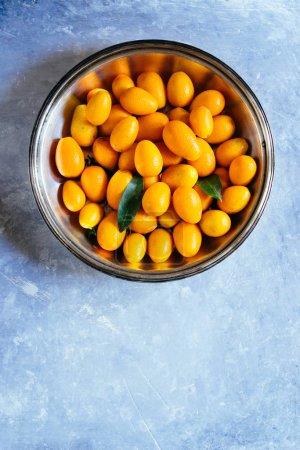 Photo pour Vue du haut de Kumquats délicieux mûrs sur la table en béton - image libre de droit