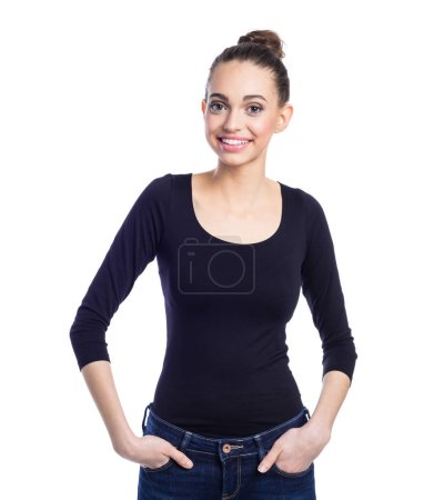 Photo for Portrait of friendly young woman wearing black top and jeans, standing with hands in pockets and smiling at camera. Studio shot against white background. - Royalty Free Image