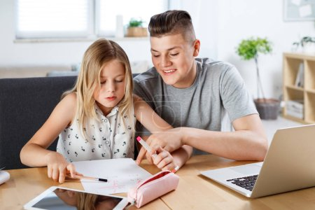 Photo pour Garçon et fille assis à la table à la maison. Frère aider son siter avec le travail à domicile . - image libre de droit
