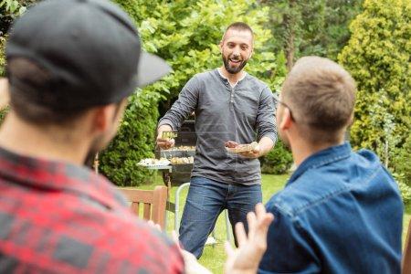 Photo pour Amis, avoir la fête en plein air dans le jardin, un homme servant une cuisine - image libre de droit