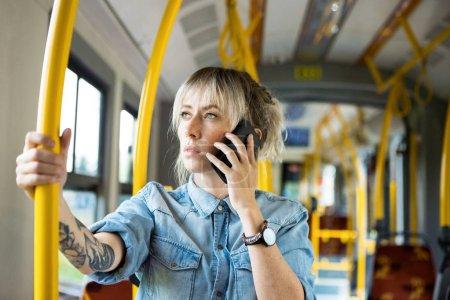 Photo pour Young woman in city transport, talking on mobile phone. - image libre de droit