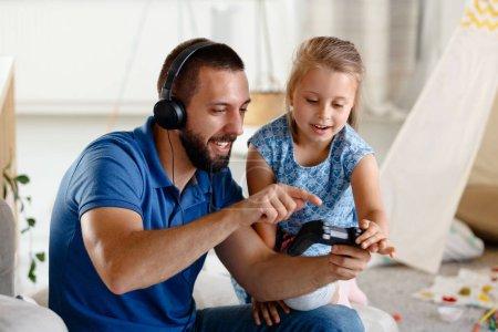 Photo pour Jeune père jouant à des jeux vidéo avec sa fille ensemble, assis dans le salon du canapé et s'amusant . - image libre de droit