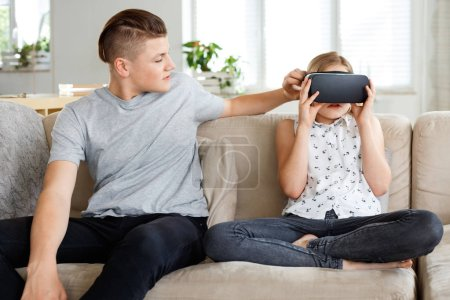 Photo for Cute girl sitting on sofa at home and using virtual reality goggle. Older brother sitting next to her. - Royalty Free Image