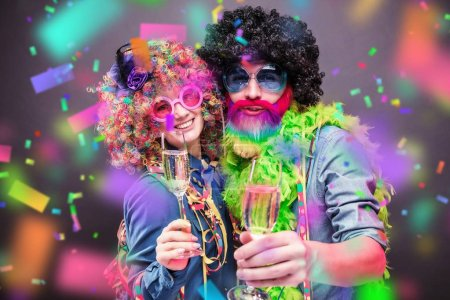 Photo for Happy man and woman wearing color wigs with party items - Royalty Free Image