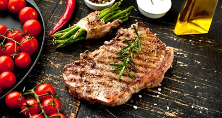 Photo for Fresh grilled meat. Grilled beef steak medium rare on wooden cutting board. Top view. - Royalty Free Image