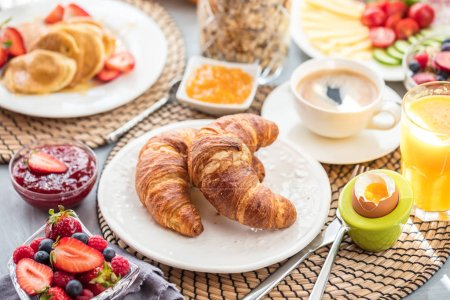 Photo for Breakfast served with coffee, orange juice and croissants - Royalty Free Image