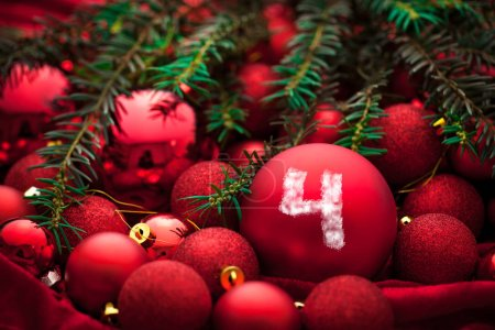 Advent decoration with red Christmas baubles and fir tree branches