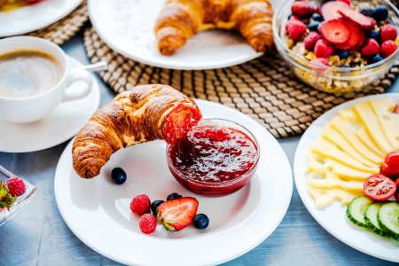 Photo for Breakfast served with coffee, orange juice, croissants, cereals and fruits. Balanced diet. - Royalty Free Image