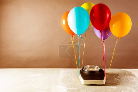 Photo for Bathroom scales with colorful balloons. Slimming concept - Royalty Free Image