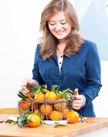 Manos de mujer con cesta de hierro con espacio de copia de clementina fresca