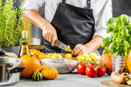 Photo pour Chef cuisinier préparant des légumes dans sa cuisine - image libre de droit