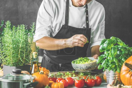 Photo for Chef cook preparing vegetables in his kitchen - Royalty Free Image