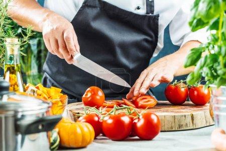 Chef cuisinier prépare des légumes dans sa cuisine
