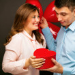 Young couple with heart shaped red balloons near g...