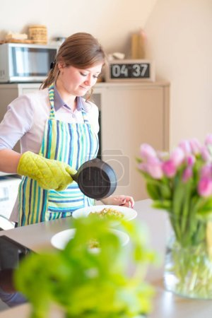 Photo for Smiling young woman in apron cooking in kitchen - Royalty Free Image