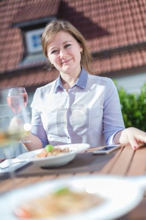 Photo for Attractive young woman holding glass of wine while sitting at table with tasty meal outdoor - Royalty Free Image
