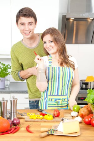 Photo for Happy young couple cooking at kitchen together - Royalty Free Image