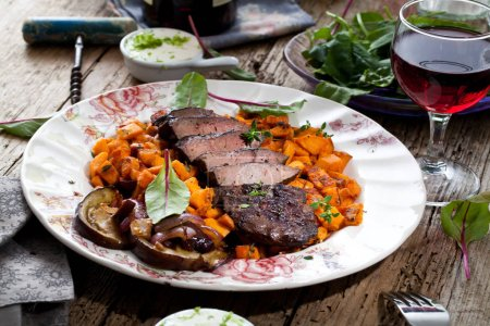 Photo for Close-up view of gourmet dish with roasted beef liver and vegetables on plate on wooden table - Royalty Free Image