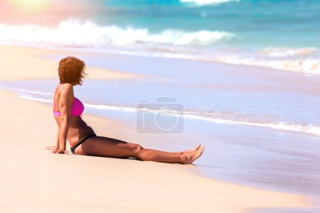 Photo for Side view of young woman in bikini resting on a Porto Santo madeira beach. - Royalty Free Image