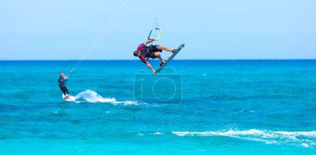 Foto de Kiteboarders kitesurfistas atletas que realizan trucos de kitesurf kiteboarding - Imagen libre de derechos