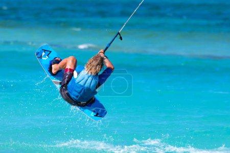 Photo pour Kiteboarder kitesurfer athlète effectuant des tours de kitesurf de kitesurf décroché - image libre de droit
