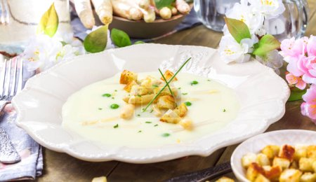 Photo for Close-up view of plate with light creamy asparagus soup flavoured with chicken stock, sour cream and basil on table - Royalty Free Image