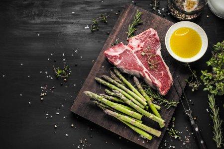 Photo pour Vue du dessus du barbecue brut T-bone steak avec asperges vertes, huile et herbes sur la table - image libre de droit