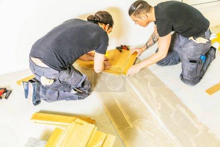 Foto de Vista de gran angular de los trabajadores que instalan suelo de parquet de roble durante la mejora del hogar. - Imagen libre de derechos