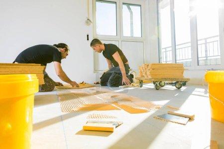 Foto de Trabajadores masculinos profesionales que instalan suelo de parquet de roble durante la mejora del hogar - Imagen libre de derechos