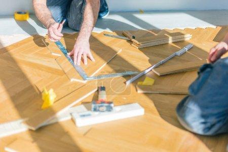 Foto de Tiro con cuerdas de los trabajadores que instalan suelo de parquet de roble durante la mejora del hogar. - Imagen libre de derechos