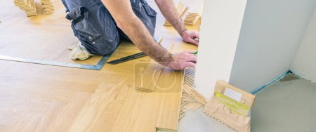 Photo for Worker varnishing oak parquet floor during home improvement - Royalty Free Image