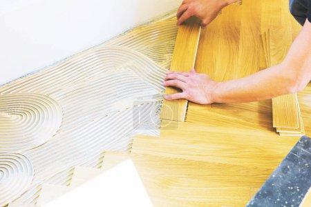 Foto de Tiro de roble de hombre que instala suelo de parquet de roble durante la mejora del hogar. - Imagen libre de derechos